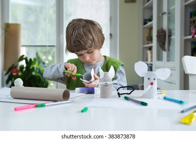 Little boy being creative making homemade do it yourself paper toys. Supporting creativity, learning by doing, learning through experience. Helping child gain access to a creative way of seeing.