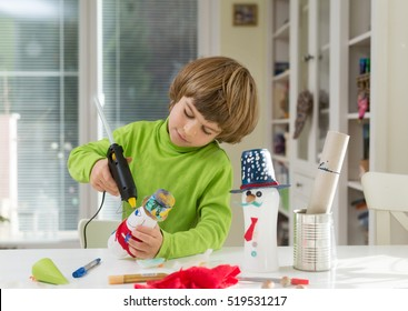 Little boy being creative making do-it-yourself toys out of yogurt bottle and paper using hot melt glue gun. Supporting creativity, hand craft. Creative leisure for children indoors.