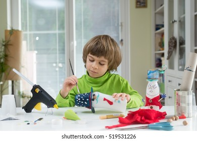 Little boy being creative making homemade do-it-yourself toys out of yogurt bottle and paper. Supporting creativity, learning by doing, hand craft. Helping child gain access to creative way of seeing.