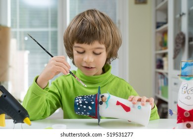 Little boy being creative making homemade do-it-yourself toys out of yogurt bottle and paper. Supporting creativity, learning by doing, hand craft. Creative leisure for children indoors.