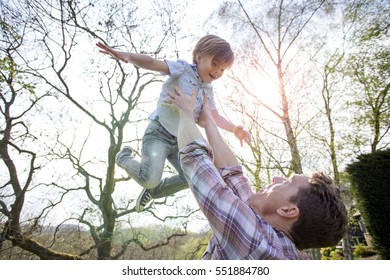 Little boy is being lifted in to the air by his father. He has his arms outstretched and is laughing while looking at his father.