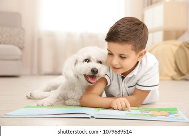 Little boy and bichon frise dog reading book at home