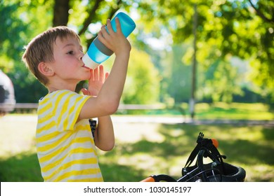 Little boy with bicycle drinks water in summer park