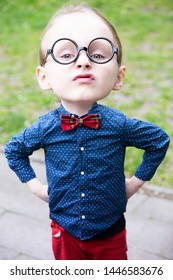 little boy with big head and glasses looking arrogant standing outdoors