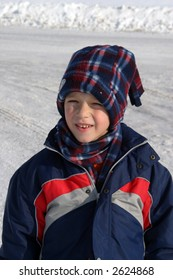 Little boy with a big smile having fun on the snow