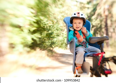 Little boy in bike child seat outdoors in motion blur by lensbaby