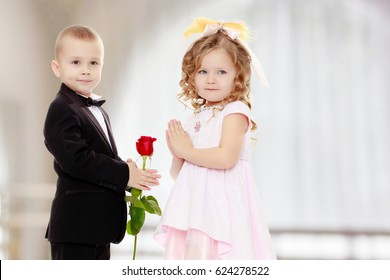 Little boy in black suit with bow tie gives a big red rose charming little girl.
