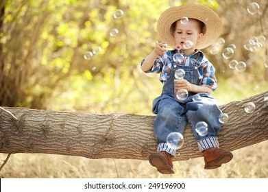 Little boy blowing bubbles mylnyie on a tree branch on a sunny day
