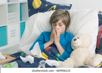 Little boy blowing his nose lying sick in bed
