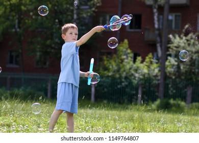 Little boy blowing soap bubbles in summer park