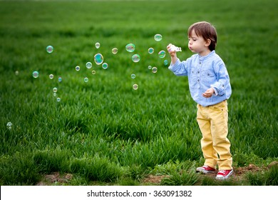 Little boy blowing soap bubbles, closeup portrait