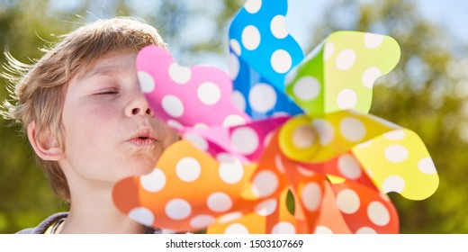 Little boy blows against a colorful windmill in summer at summer camp in the sunshine