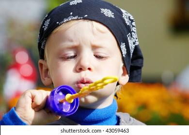 A little boy blows bubbles