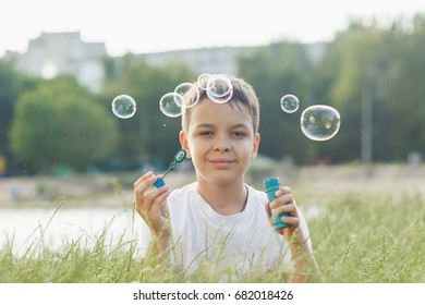 Little boy blows soap bubbles, soft focus background
