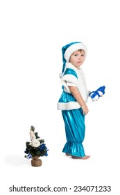 Little boy in blue Santa suit walks away from a small Christmas tree isolated on white background