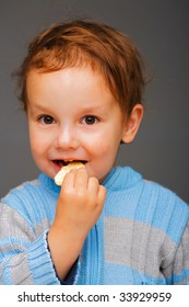 Little boy in a blue sweater eating a cookie