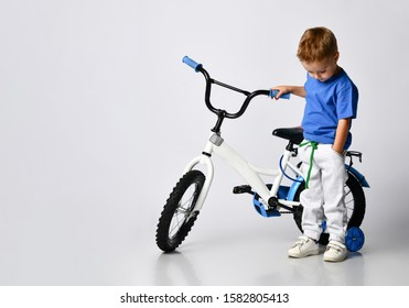 little boy in a blue T-shirt stands near his new childrens bike with extra wheels. on a light isolated background