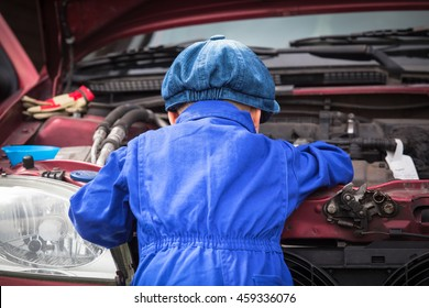 Little boy in blue workwear overall in front of open engine compartment doing some maintenance work at the car/Little Mechanic