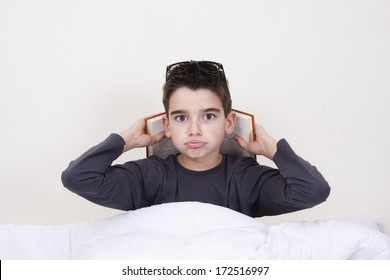 Little boy with book and expressions in bed