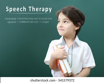 Little boy with books at school. Text SPEECH THERAPY on chalkboard background