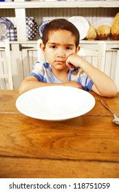 Little boy with bored grumpy expression sitting at a wooden table in front of a large empty white bowl waiting for breakfast