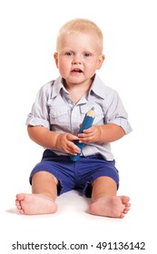 A little boy in a bright shirt with stripes and blue shorts sitting with big pencil isolated on white background.