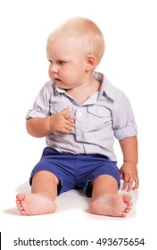 A little boy in a bright shirt with stripes and blue shorts sitting isolated on white background.
