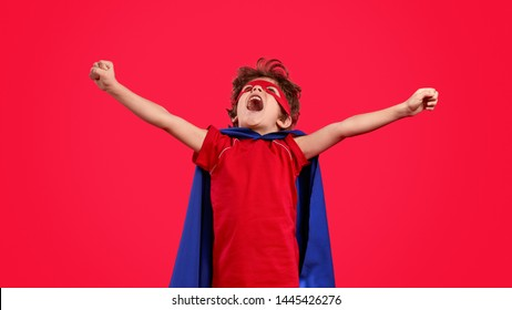 Little boy in bright superhero costume looking up and yelling in excitement while stretching out arms against red background