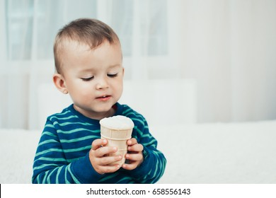 The little boy in the bright white room eating ice cream in waffle Cup