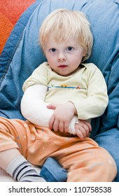 Little boy with a broken arm sitting on a couch
