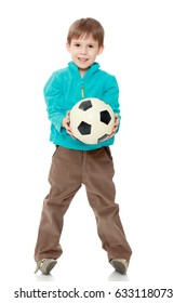 Little boy in brown pants and blue shirt playing with a soccer ball.Isolated on white background.