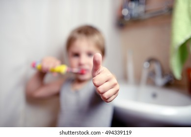 Little boy brushing teeth in bath with electric brush also shows thumbs up