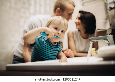 Little boy brushing teeth with his parents in bathroom.