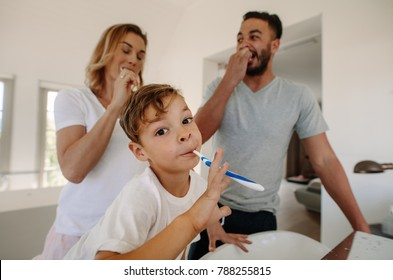 Little boy brushing teeth with his parents in bathroom. Family brushing teeth together in bathroom.