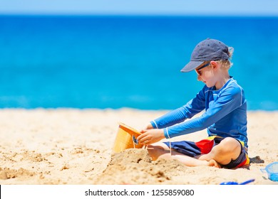 little boy building sand castle, wearing rashguard for sun protection, enjoying relaxing summer vacation at lanai island, hawaii, copy space on left