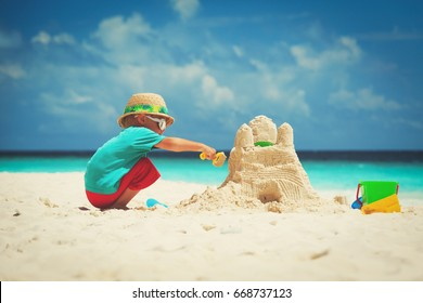 little boy building sand castle on beach