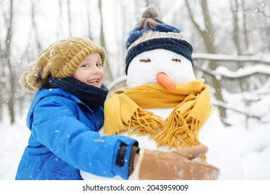 Little boy building snowman in snowy park. Child embracing snowman wearing hat and scarf. Active outdoors leisure with family with children in winter. Kid during stroll in a snowy winter park