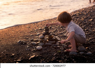 Little boy building a stone castle on a seaside. Image with selective focus and toning.