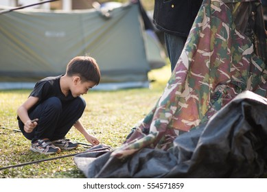 Little boy building a tent for camping with family holiday summer time