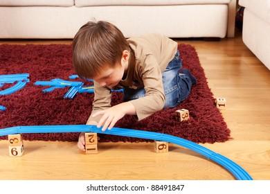 Little boy is building toy railroad using bricks