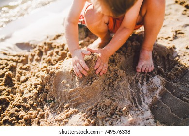 a little boy builds figures from the sand on the shore of the pond at sunset of the day, hands dig up the sand in a crisp plan