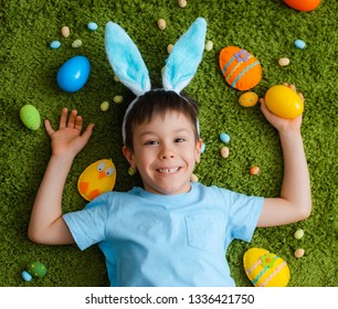 Little boy in bunny ears are playing with Easter eggs. Kids celebrating Easter. Children on Easter egg hunt. Home decoration, pastel bunny banner.