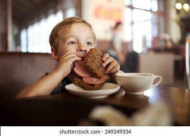 Little boy in a cafe during lunch. Hungry kid eating sausage from his sandwich