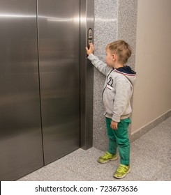 The little boy is calling the elevator.