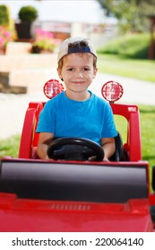 Little boy in cap drive electric vehicle toy