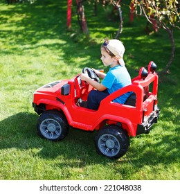 Little boy in cap drive electrical vehicle in garden, outdoor portrait