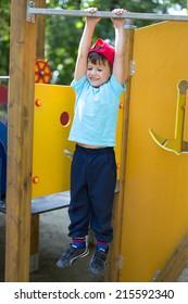Little boy in cap hanging at playground, outdoor portrait