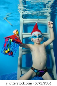 A little boy in a cap Santa Claus with a gift in hand sits underwater on the stairs at the bottom of the pool. The view from under the water. Close-up. Vertical orientation