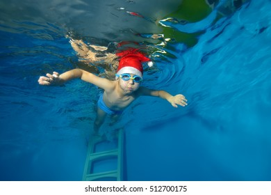 A little boy in a cap Santa Claus swims underwater with outstretched arms on a blue background. The view from under the water at the bottom. Horizontal orientation
