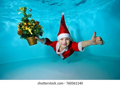 A little boy in a cap Santa Claus swimming underwater with outstretched arms, and with a Christmas tree in hand on blue background, looking at camera and smiling. Portrait. Shooting under water